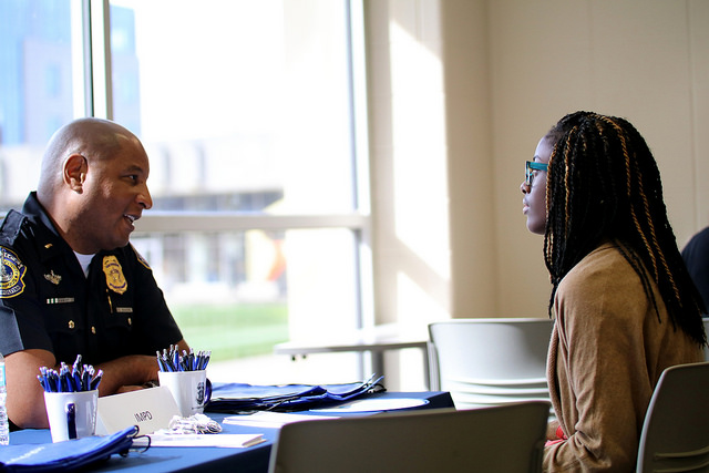 A cop talking to a student about her future career options.